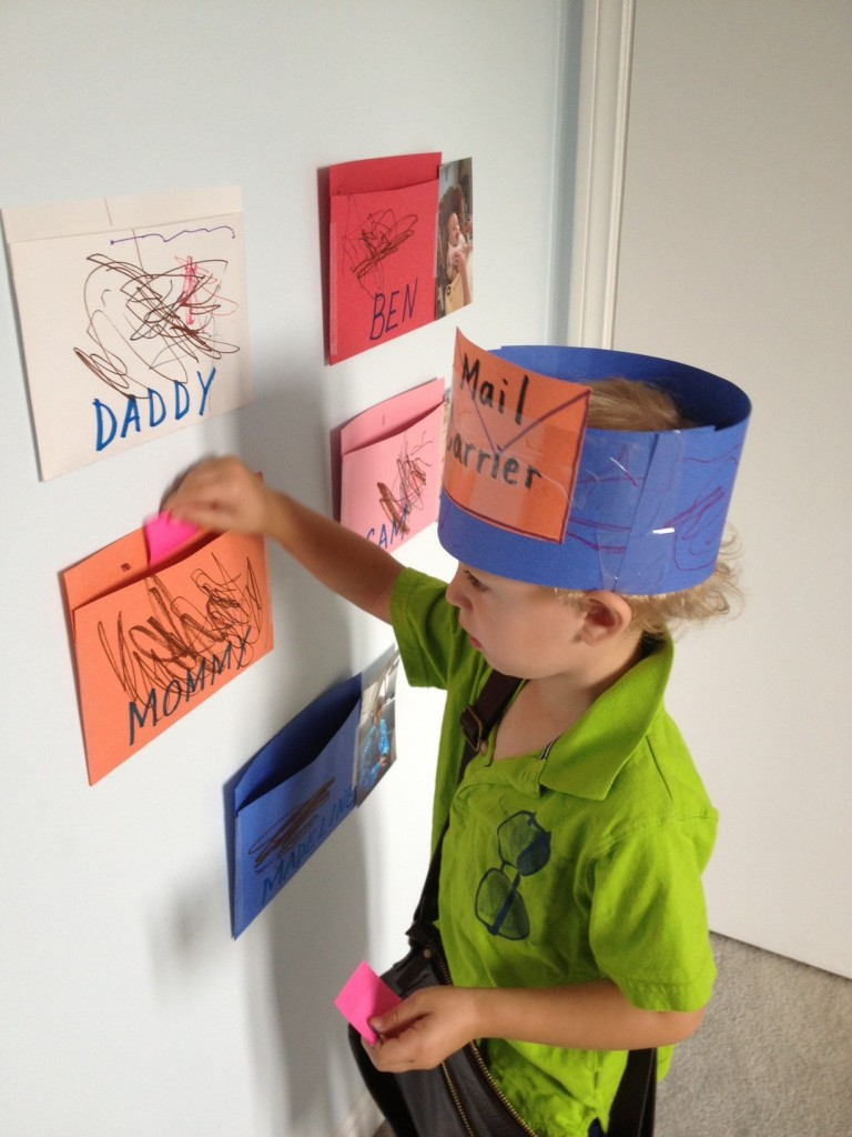 My little 3 year old playing with his preschool post office! Popping homemade letters into our colourful homemade envelopes. He is wearing his homemade mail carrier hat too!
