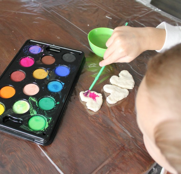 preschooler painting salt dough with water colors