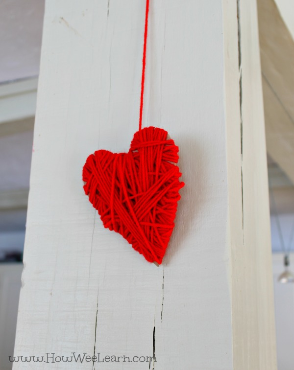 Wrapping hearts with yarn as a Valentine's day craft for preschooler. #easycraft #preschool #heartcraft #valentinesday #valentinecraft