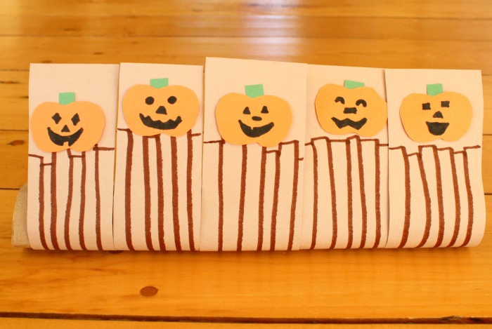 5 little pumpkins sitting on a gate!
