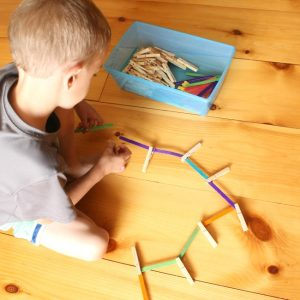 Invitation to build with popsicle sticks and clothespins