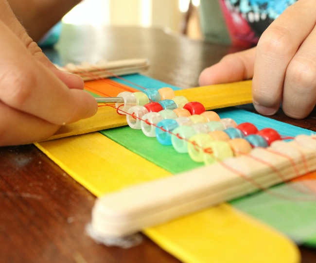 A DIY bead loom made from popsicle sticks. Perfect for making homemade beaded bracelets. #DIY #tutorial #beadloom #bracelets #ponybeads #crafts