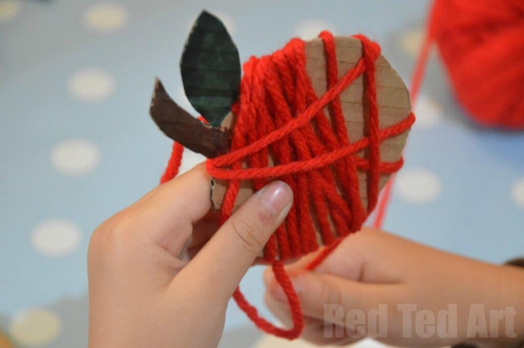 This yarn apple craft is great for fine motor skills. Create just one or make multiples for a fall apple garland. Here you will find cute and simple apple crafts for kids, toddlers and preschoolers. #applecraft #fallcrafts #fallcraftsforkids #autumncrafts #preschoolcrafts #howweelearn