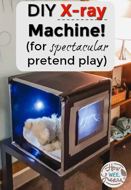 A stuffed bear in a homemade x-ray machine made from a cardboard box in a preschool classroom