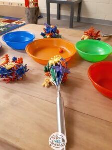 a whisk with plastic animals stuck inside for preschool fine motor play